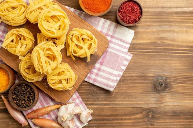 Bovenaanzicht rauwe deeg bloem gevormde pasta met verschillende kruiden op een bruine achtergrond deeg maaltijd voedseldeegwaren