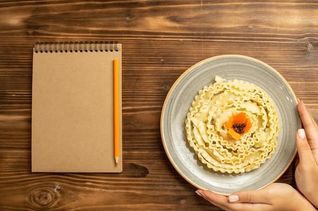 Bovenaanzicht rauwe deeg pasta gevormd binnen plaat op de bruine tafel deeg rauwkost pastamaaltijd