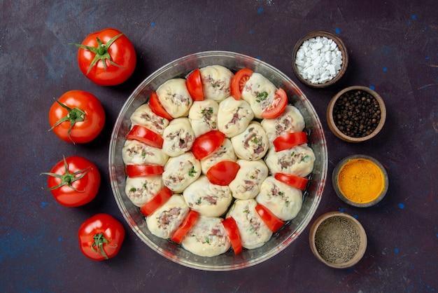 Bovenaanzicht rauwe deegstukken met gehakt en tomaten op donkere maaltijd keukenschotel keuken foto voedselsalade