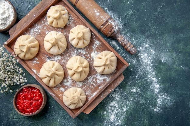 Bovenaanzicht rauwe dumplings met vlees binnen op de donkere achtergrond maaltijd koken kleur bloem peper schotel deeg vlees