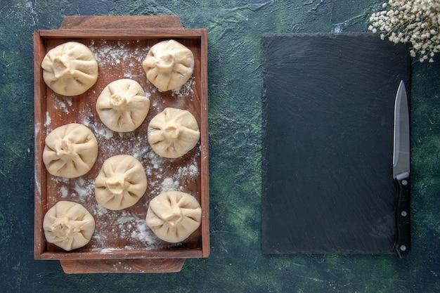 Bovenaanzicht rauwe dumplings met vlees binnen op donkere achtergrond kleur maaltijd peper deeg vlees schotel koken