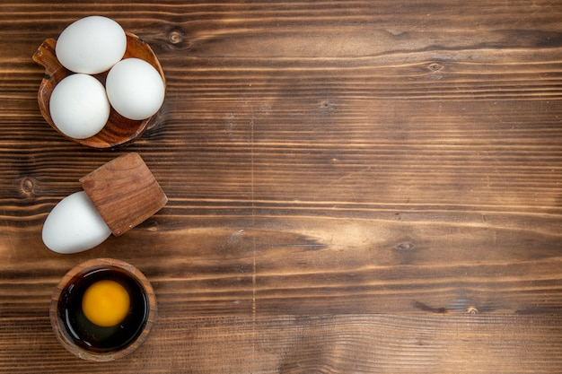 Bovenaanzicht rauwe eieren hele producten op een bruine achtergrond ei voedsel maaltijd ontbijt lunch brood gezondheid