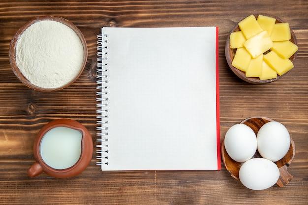 Bovenaanzicht rauwe eieren met melk en gesneden kaas op tafel maaltijd ontbijt deeg