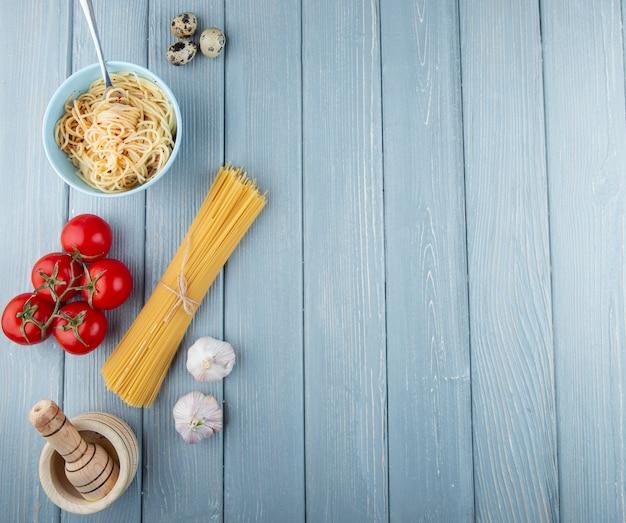 Bovenaanzicht rauwe en gekookte spaghetti met verse tomaten en knoflook op een houten rustieke achtergrond