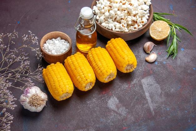 Bovenaanzicht rauwe gele likdoorns met verse popcorn op donkere oppervlakte snack popcorn film plant maïs