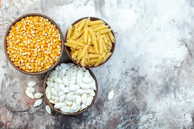 Bovenaanzicht rauwe gele likdoorns met zaden en pasta in platen op lichte ondergrond