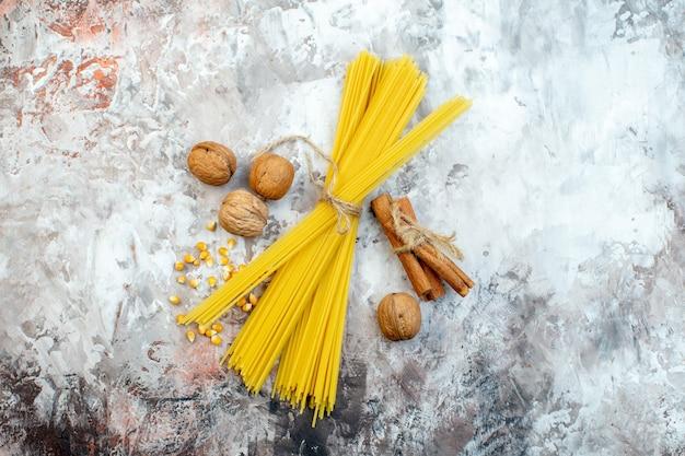 Bovenaanzicht rauwe gele pasta met walnoten op lichte ondergrond