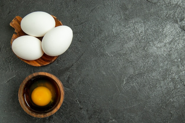 Bovenaanzicht rauwe hele eieren op grijze achtergrond ei ontbijtmaaltijd eten rauw