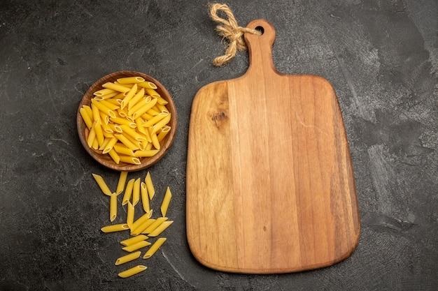 Bovenaanzicht rauwe italiaanse pasta in bruine plaat op grijs