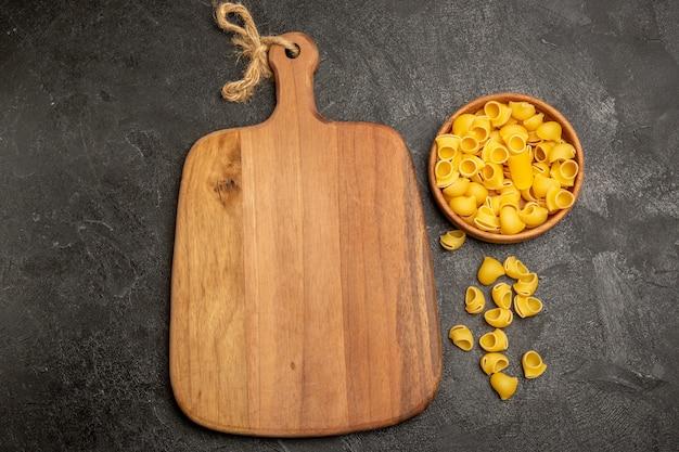 Bovenaanzicht rauwe italiaanse pasta in bruine platen op grijs bureau