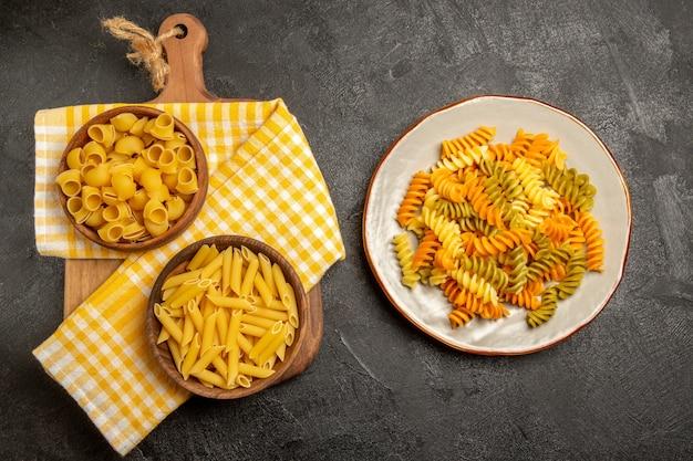 Bovenaanzicht rauwe italiaanse pasta in bruine platen op het grijs