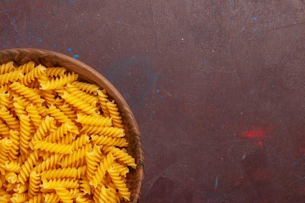 Bovenaanzicht rauwe italiaanse pasta in houten dienblad op donkere ruimte