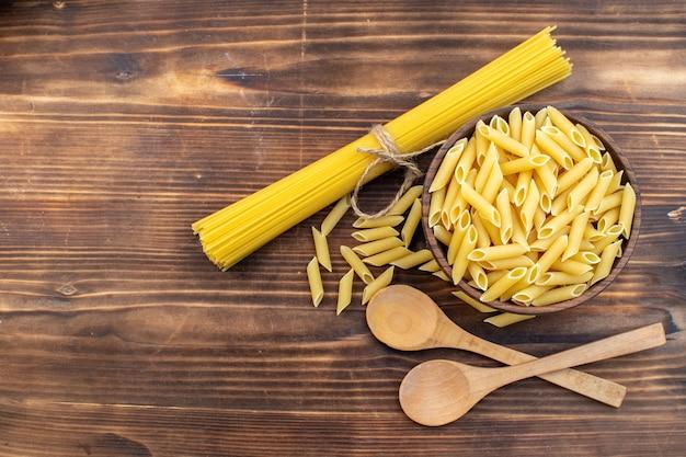 Bovenaanzicht rauwe italiaanse pasta lang en weinig gevormd op bruin oppervlak