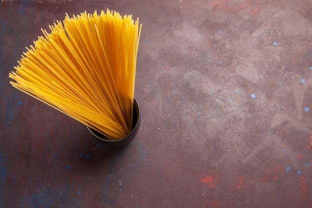 Bovenaanzicht rauwe italiaanse pasta lang gevormd geel gekleurd op de donkere achtergrond pasta italië deeg maaltijd rauwkost kleur
