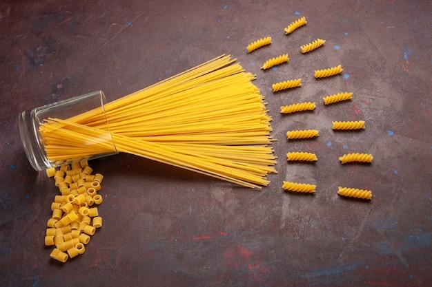 Bovenaanzicht rauwe italiaanse pasta lang gevormd geel gekleurd op de donkere achtergrond pasta italië deeg maaltijd voedsel kleur