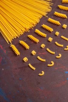 Bovenaanzicht rauwe italiaanse pasta lang gevormd geel gekleurd op donkere achtergrond pasta italië deeg maaltijd rauwkost
