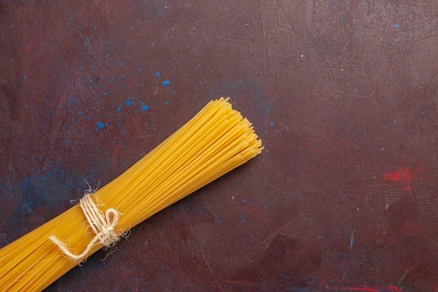 Bovenaanzicht rauwe italiaanse pasta lang gevormd op de donkerpaarse achtergrond maaltijd eten deeg pasta rauw