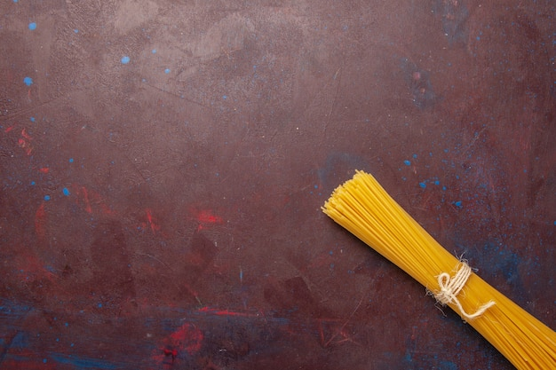 Bovenaanzicht rauwe italiaanse pasta lang gevormd op donkere bureau maaltijd eten deeg pasta rauw Gratis Foto