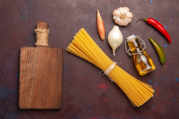 Bovenaanzicht rauwe italiaanse pasta lang gevormd op donkere paarse achtergrond maaltijd eten deeg pasta rauwe groente