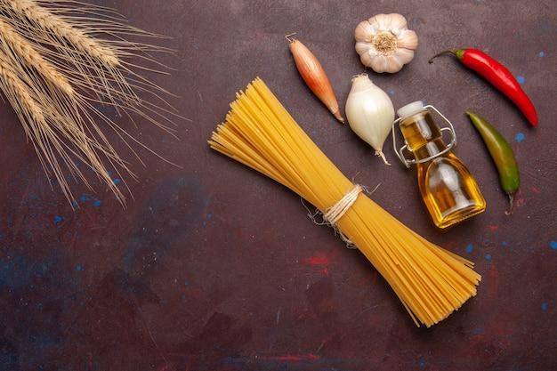 Bovenaanzicht rauwe italiaanse pasta lang gevormd op donkerpaarse achtergrond maaltijd eten deeg pasta rauwe groenten
