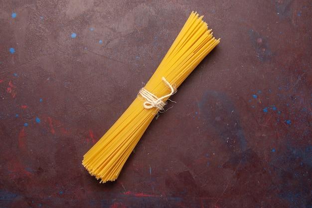 Bovenaanzicht rauwe italiaanse pasta lang gevormd op een donkere achtergrond maaltijd eten deeg pasta rauw