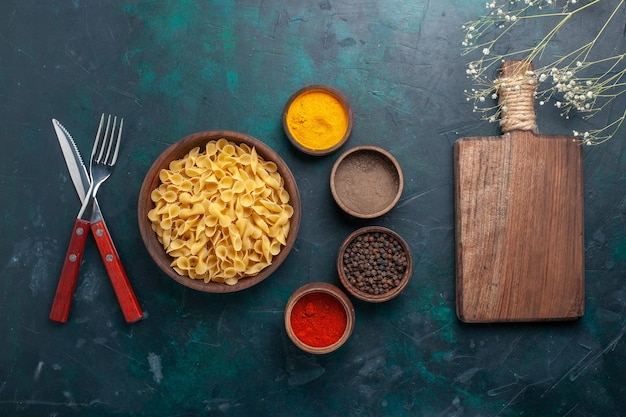 Bovenaanzicht rauwe italiaanse pasta met kruiden op donkerblauwe achtergrond ingrediënt voedsel maaltijd rauw
