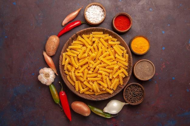 Bovenaanzicht rauwe italiaanse pasta met kruiden op donkerpaarse achtergrond pasta rauwe maaltijd voedseldeeg
