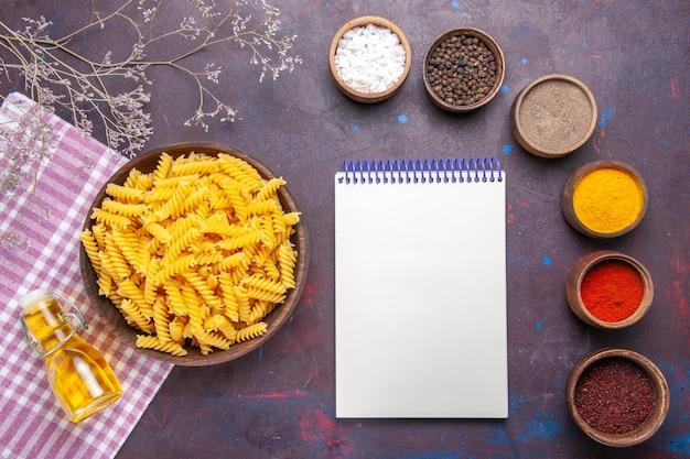 Bovenaanzicht rauwe italiaanse pasta met verschillende kruiden op de donkere kleur van het ingrediënt van de maaltijd van het voedsel van de oppervlaktedegas