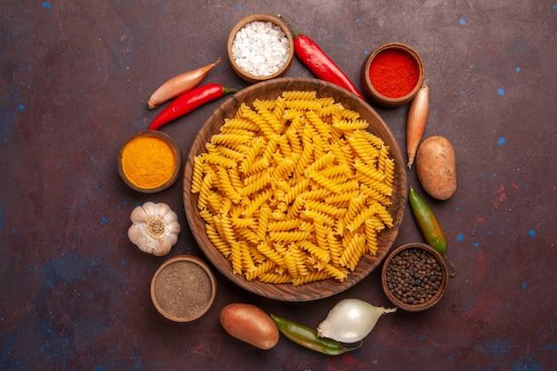Bovenaanzicht rauwe italiaanse pasta met verschillende kruiden op de donkerpaarse achtergrond pasta rauwe maaltijd voedseldeeg