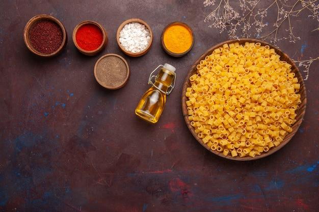 Bovenaanzicht rauwe italiaanse pasta met verschillende kruiden op donkere achtergrond pasta eten deeg diner rauw veel