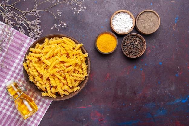 Bovenaanzicht rauwe italiaanse pasta met verschillende kruiden op donkere oppervlakte pasta voedsel maaltijd ingrediënten kleur