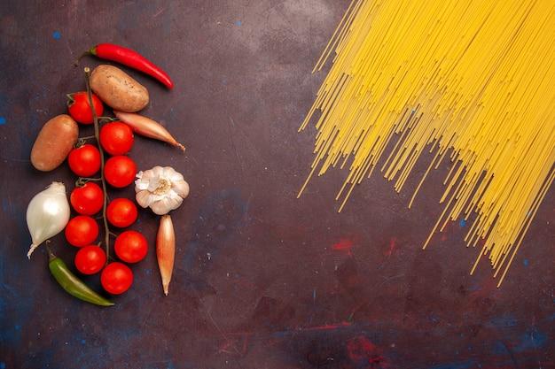 Bovenaanzicht rauwe italiaanse pasta met verse groenten op donkere achtergrond pasta italië deeg maaltijd voedselkleur