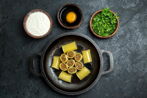 Bovenaanzicht rauwe italiaanse pasta met vlees in de pan en met groenen op donkere achtergrond pasta deeg maaltijd eten