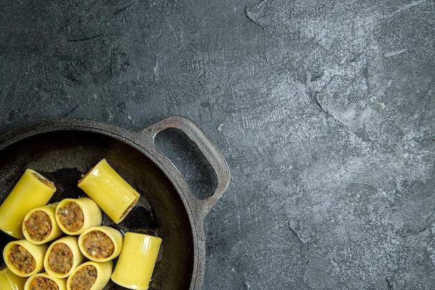 Bovenaanzicht rauwe italiaanse pasta met vlees in de pan op het donkere achtergrond pasta deeg maaltijd eten Gratis Foto