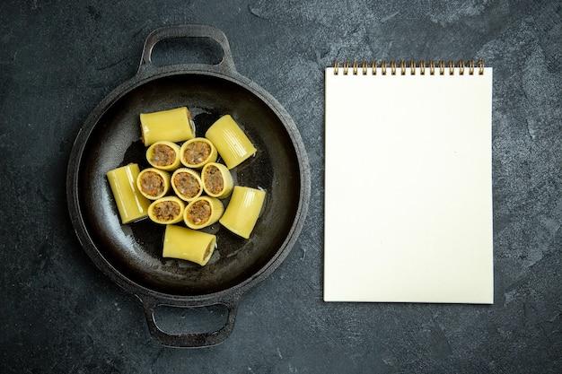 Bovenaanzicht rauwe italiaanse pasta met vlees in de pan op het donkere achtergrond pasta deeg maaltijd eten