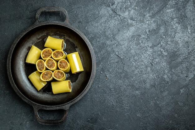 Bovenaanzicht rauwe italiaanse pasta met vlees in de pan op het donkere achtergrond rauwe deeg maaltijd pastavoedsel