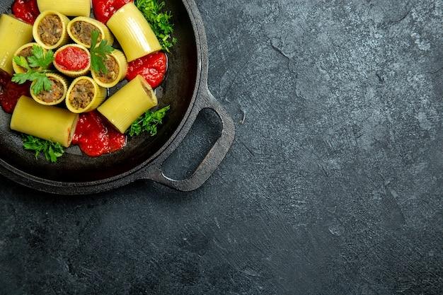 Bovenaanzicht rauwe italiaanse pasta met vleesgreens en tomatensaus in de pan op de donkere achtergrond pasta deeg maaltijd eten