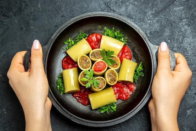 Bovenaanzicht rauwe italiaanse pasta met vleesgreens en tomatensaus in de pan op de donkere grijze achtergrond pasta deeg maaltijd eten
