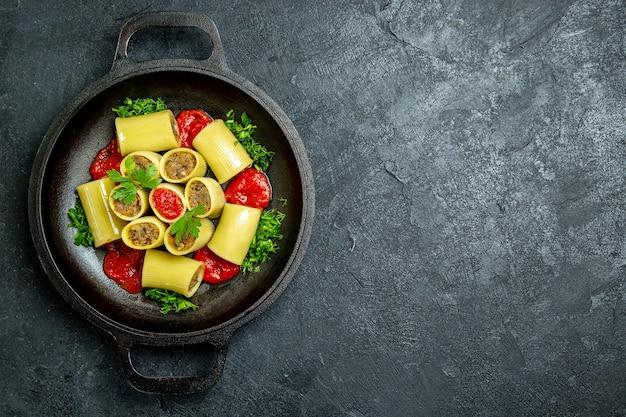 Bovenaanzicht rauwe italiaanse pasta met vleesgreens en tomatensaus in pan op een donker bureau pasta deeg maaltijd eten