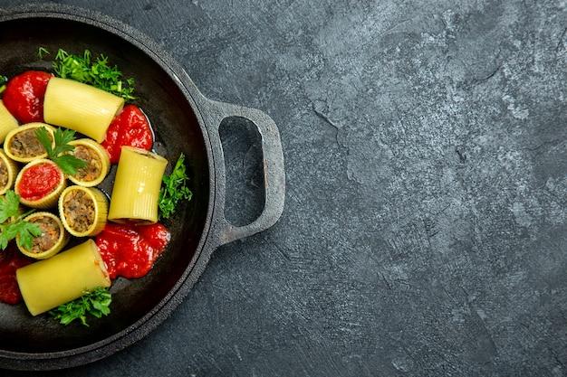 Bovenaanzicht rauwe italiaanse pasta met vleesgreens en tomatensaus in pan op een donkere vloer pasta deeg maaltijd eten