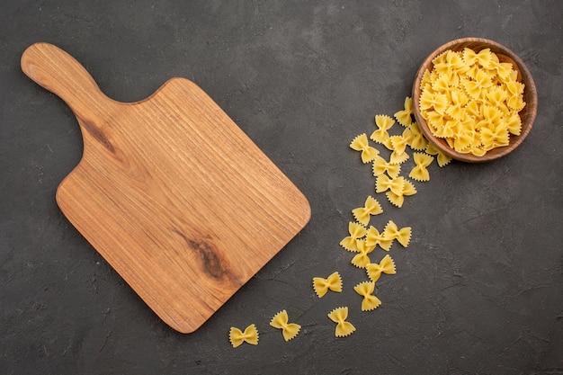Bovenaanzicht rauwe italiaanse pasta op donkere achtergrond