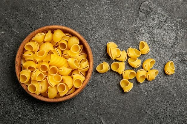 Bovenaanzicht rauwe italiaanse pasta op grijs