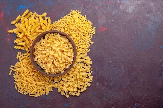 Bovenaanzicht rauwe italiaanse pasta verschillend gevormd op de donkere paarse achtergrond ingrediënt voedsel maaltijd rauw