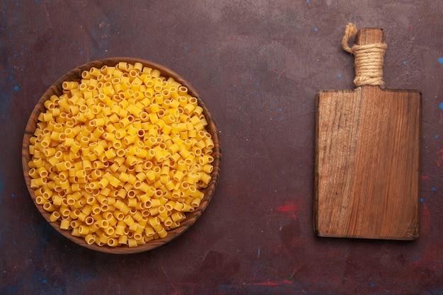 Bovenaanzicht rauwe italiaanse pasta weinig gevormd binnen plaat op donker bureau pasta maaltijd voedseldeeg veel