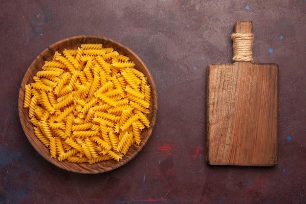 Bovenaanzicht rauwe italiaanse pasta weinig gevormd binnen plaat op donkerpaarse achtergrond pasta rauwe maaltijd voedseldeeg