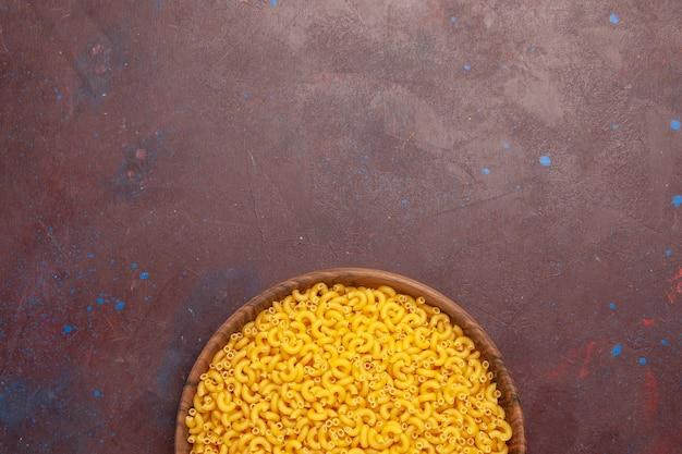 Bovenaanzicht rauwe italiaanse pasta weinig gevormd op donkere achtergrond pasta maaltijd voedseldeeg rauw