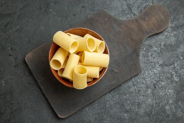 Bovenaanzicht rauwe italiaanse pasta weinig gevormd op grijs bureau rauw maaltijd eten pasta deeg