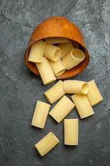 Bovenaanzicht rauwe italiaanse pasta weinig gevormd op het grijze oppervlak rauwe maaltijd eten pastadeeg
