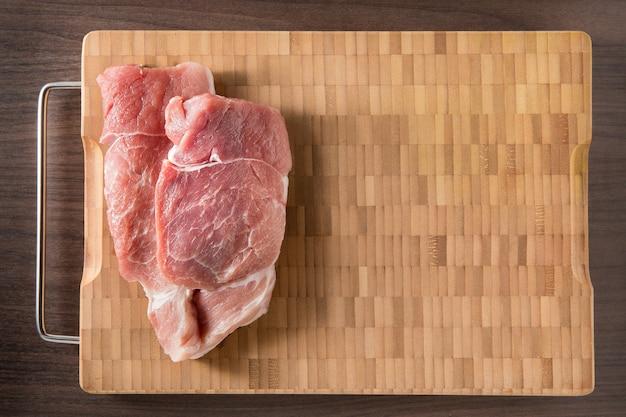 Bovenaanzicht rauwe karbonade steak op houten bamboe achtergrond met vrije tekstruimte.