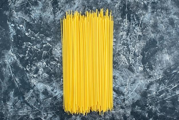 Bovenaanzicht rauwe lange pasta op de grijze achtergrond keuken pasta deeg keuken keuken kleur voedsel koken